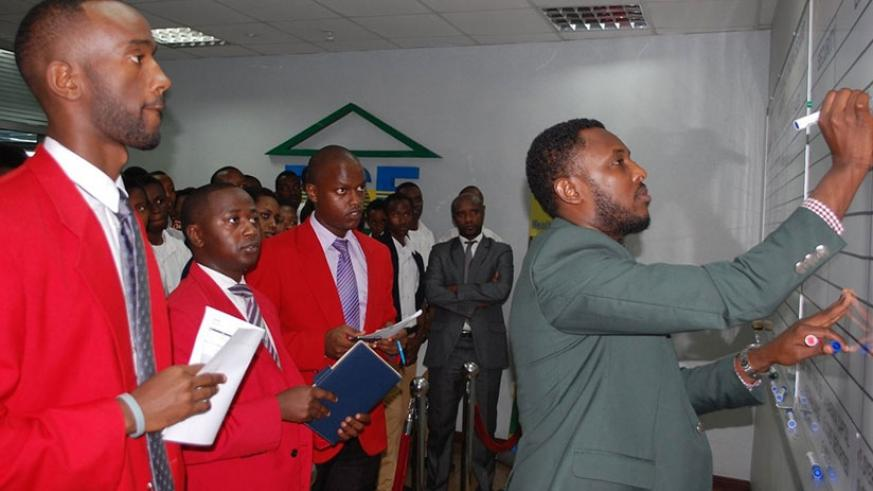 Market intermediaries during an earlier trading session. BK counter rose Rwf7 to Rwf190 yesterday. (File)