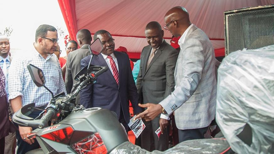 Trade and Industry minister Vincent Munyeshyaka (2ndL) and Private Sector Federation chairperson Benjamin Gasamagera (2nd R) visit Rwanda Motor Company stand during the exhibition ....