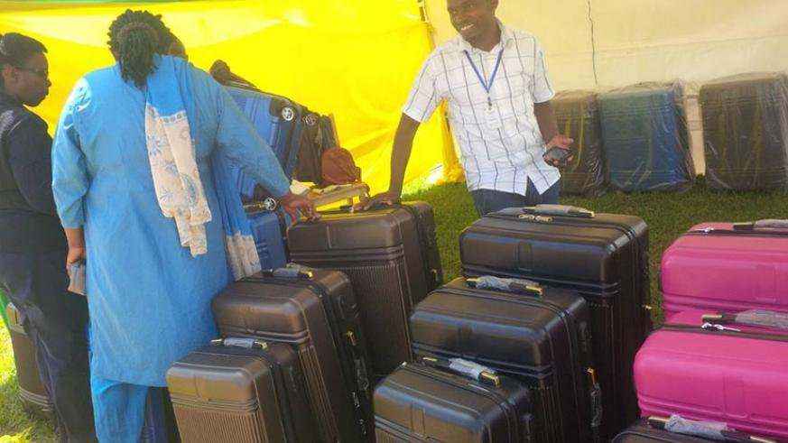 Salesmen try to convince a client to buy a suitcase.  / Joan Mbabazi.