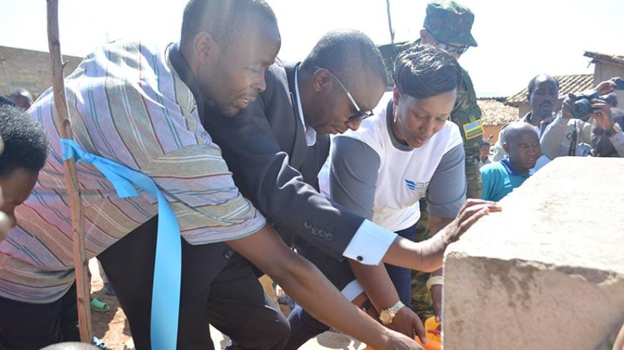 Umugwaneza (right) and Mbabazi (second left) launch the water taps as Rwoga village leaders watch on. The water point was constructed using funding from BDF. / Frederic Byumvuhore