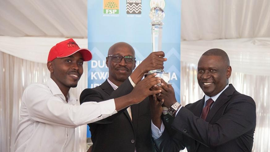 Rwanda Motorcycle Company representatives receive the Best Exhibitor's award from PSF's  Gasamagera (R) during the official closure of the Made-in-Rwanda Expo. Nadege Imbabazi.