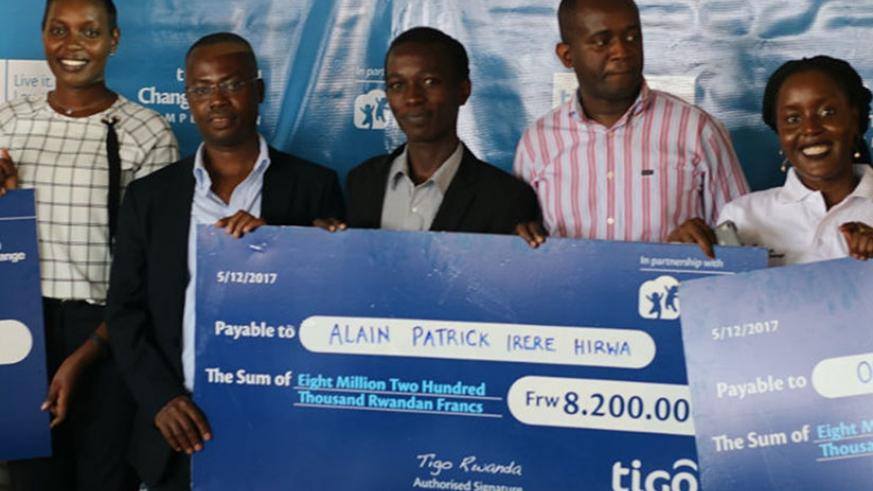 Hirwa (middle) receives a dummy cheque of his prize money from Amoateng (second left) and Reach for Change's Madzima-Bosha (right). Left is ICT ministry's Irere.   / Joan Mbabazi.