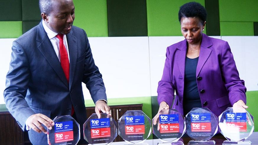 Mwangi ( left) and Pertet display the financial services sector 2017 Top Employer trophies at the firm's head office in Nairobi. / Courtesy.