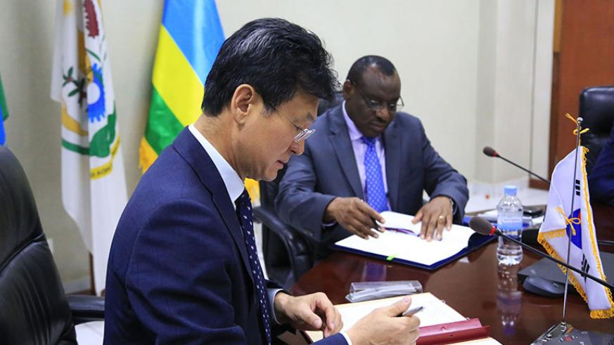 Ambassador of the Republic of Korea Kim Eung-Joong  and Minister Gatete sign the agreement in Kigali yesterday. / Sam Ngendahimana