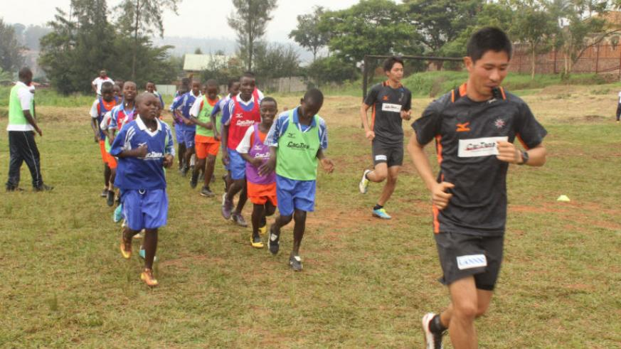 Japanese coaches Shuzo Sakamoto (in-front) and Daichi Motomatsu lead the children during the first training session.