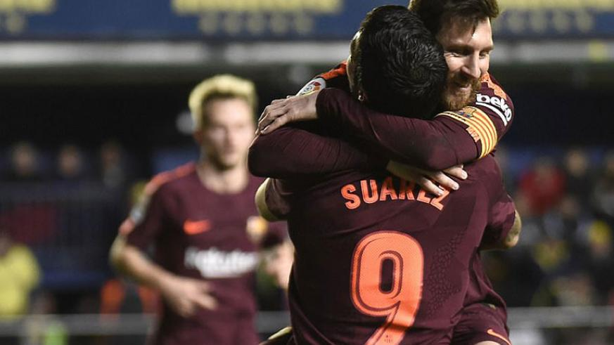 Lionel Messi receives a bear hug from team-mate Luis Suarez after doubling Barcelona's advantage late on. / Internet photo