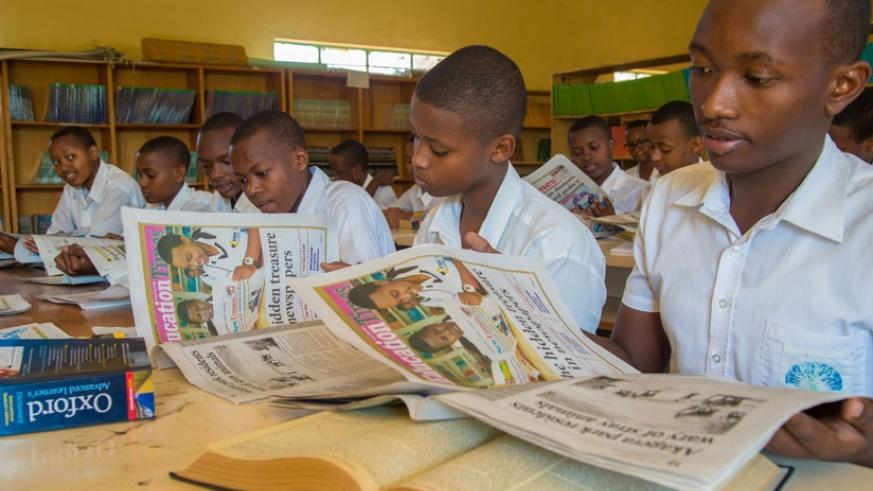 Students reading copies of The New Times (File)