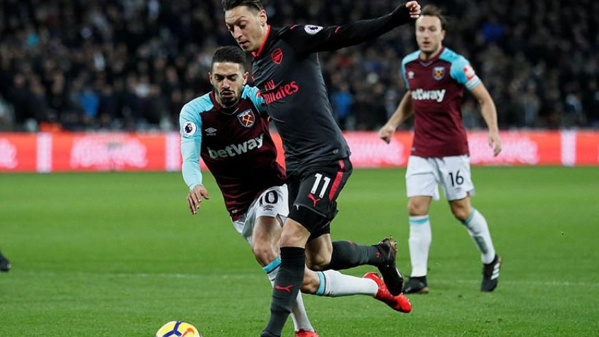 Arsenal playmaker Mesut Ozil takes the ball past West Ham attacking midfielder Lanzini as he tries to spark an attack. / Net photo