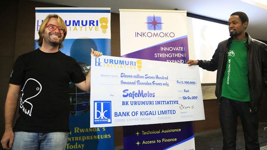 Officials from SafeMotos, Barrett Nash (left) and Eric Joseph, display a dummy cheque for the Rwf11.7 million interest-free loan they won in the BK Urumuri Initiative competition. ....