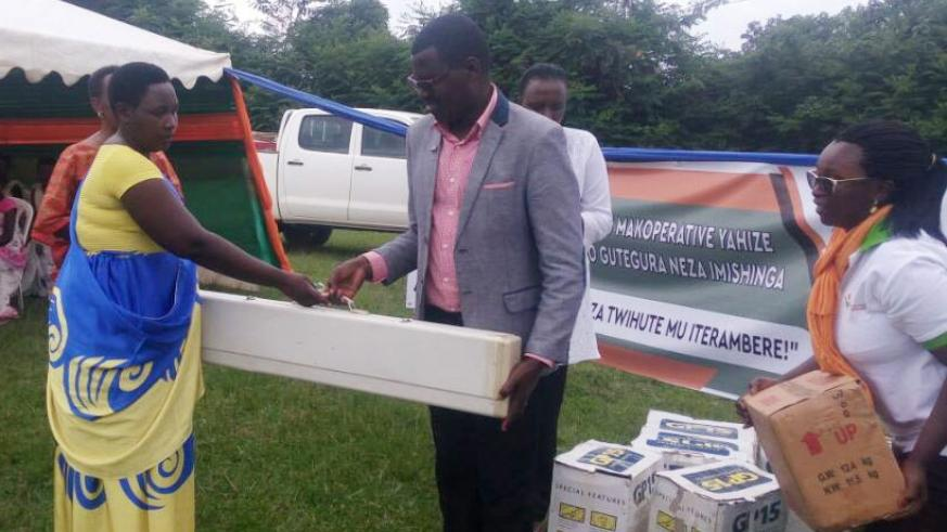 Bisiza handing over a knitting machine to one of the cooperatives. / Michel Nkurunziza