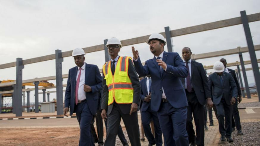President Kagame, flanked by AfriPrecast Ltd proprietor and chairman Alex Bayigamba (left), an engineer and officials on a guided tour of the facility located on the outskirts of t....
