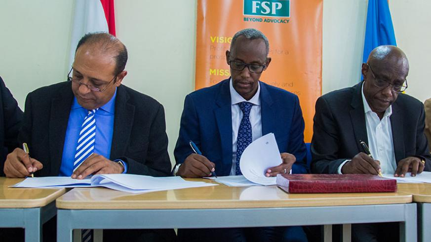 Dr Mohamed Galal,(L)  sign documents with, PSF Chief Executive Officer, Stephen Ruzibiza (C) and Philibert Afrika board chairman of University of Kigali. / Timothy Kisambira