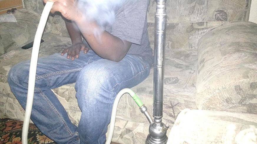 A person smokes shisha. Inset: A package of flavoured fruit used in shisha smoking. Courtesy.