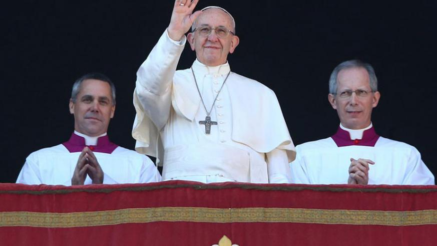 """Pope Francis waves as he leads the """"Urbi et Orbi"""" (to the city and the world) message from the balcony overlooking St. Peter's Square at the Vatican yesterday. / Net photo"""