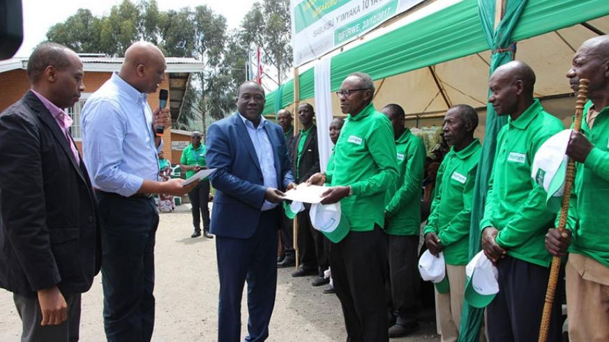 Gatare (L), Kalima (C) and Northern Province governor JMV Gatabazi give certificates of appreciation to the former miners for their contribution to national development. (Courtesy photos)