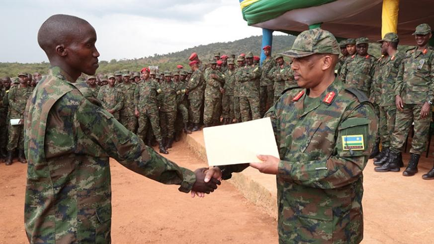 Gen Nyamvumba rewards Private Patrick Nkurunziza, who emerged the best from the 09/2017 intake, after the one-year military training. Courtesy.