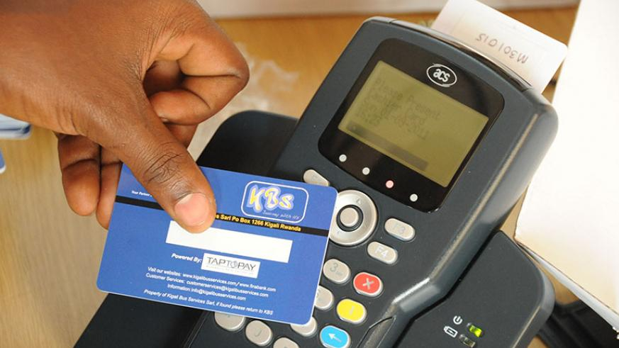 A passenger uses a Tap and Go card to pay his fare as he boards a bus. AC Group, the brains behind the cashless mode of public transport payment say this year, 97% of people in Kig....
