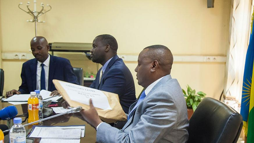 Munyakazi (right) after receiving results from REB DG Janvier Gasana (middle) at the ministry on Tuesday. / Nadege Imbabazi