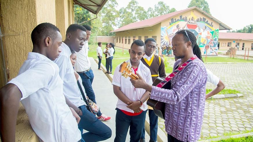 Jacques Murigande (Mighty Popo), director of music department at Nyundo School of Art, teaches some of the students how to play a guitar, last month. File.