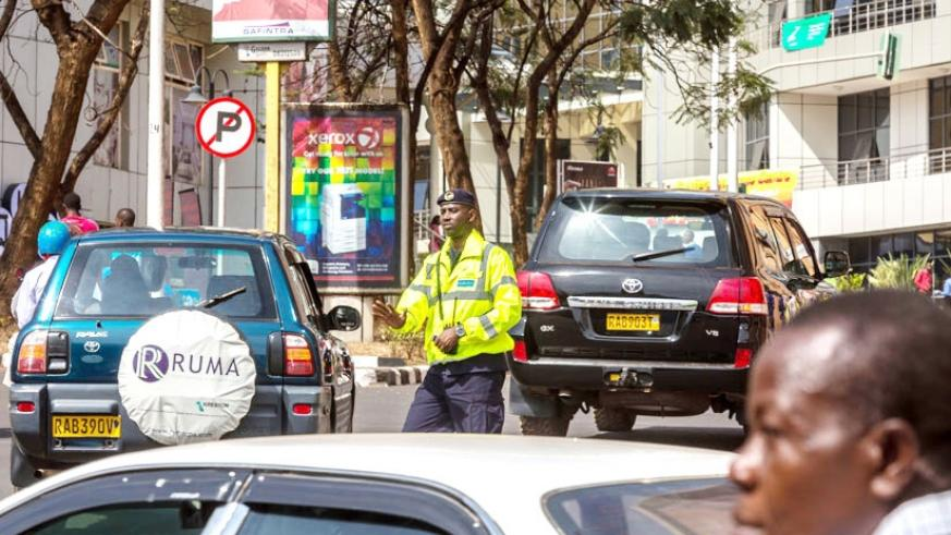 A traffic police officer guides motorists in Kigali's Central Business District. Motorists have decried the recent increase of insurance premiums by 73 per cent. File.