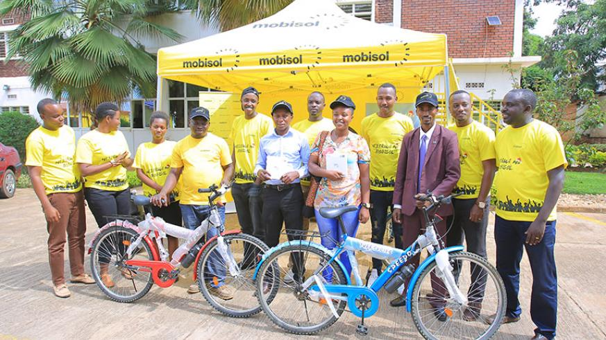 Mobisol officials pose for a picture with some of the first monthly draw winners. / Courtesy.