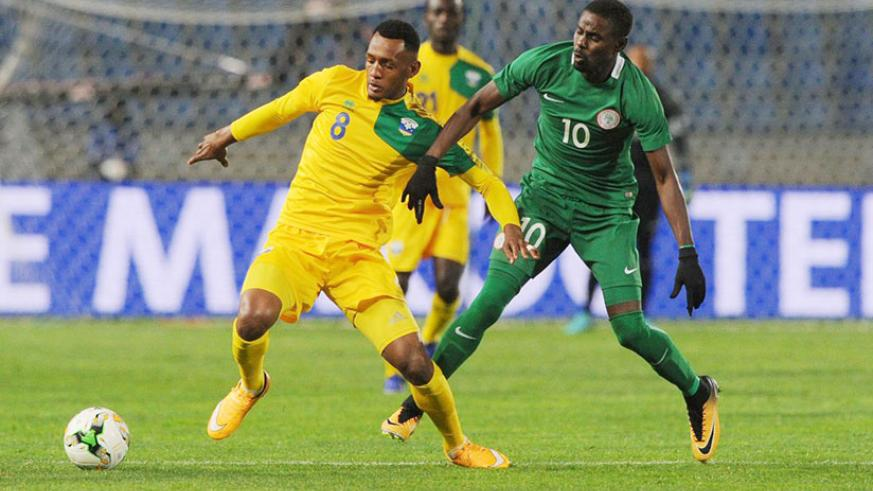 Amavubi's Ali Niyonzima (left) holds off a Nigerian player during their Group C match at Grand Stade de Tanger. Courtesy.