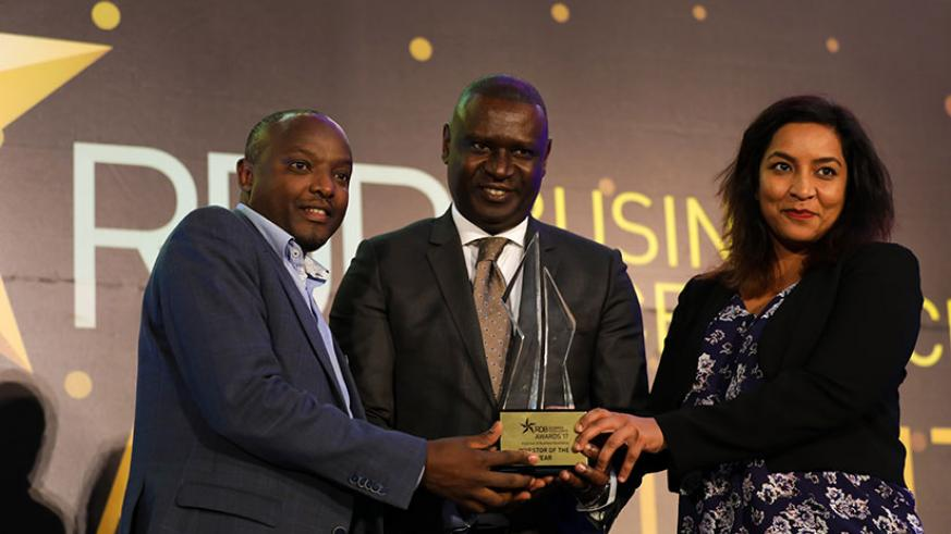 PSF chairman Benjamin Gasamagera (C) hands over the Investor of the year award to Prosper Ndayiragije, Country manager of Improved foods - Rwanda Ltd (L) and Darshana Josh, company....
