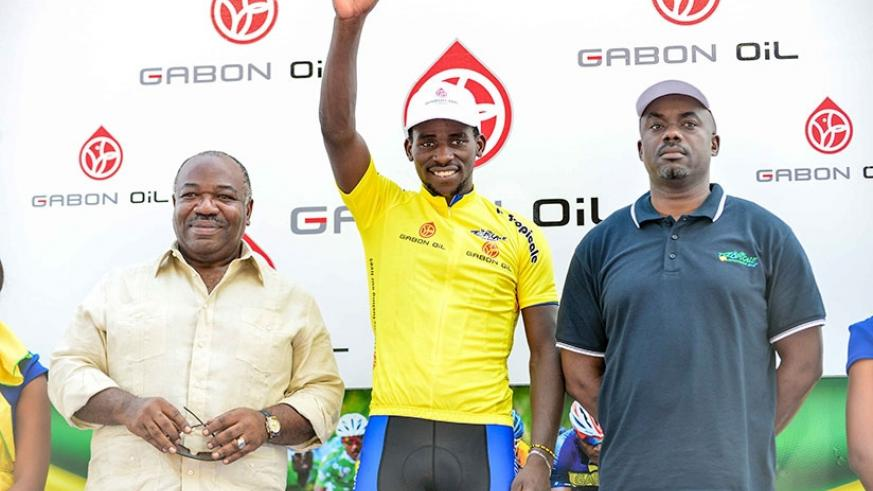 Team Rwanda's Joseph Areruya is joined on the podium by Gabonese President, Ali Bongo Ondimba (L) after he was crowned the winner of the 2018 edition of La Tropicale Amissa Bongo y....
