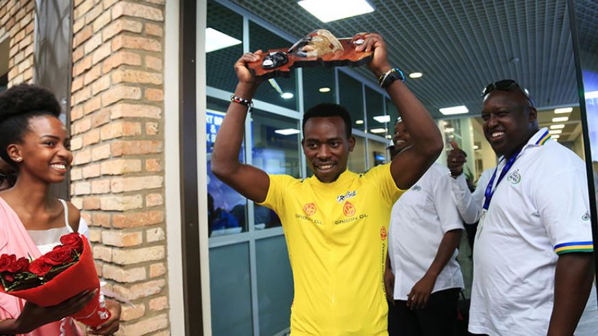 Areruya shows off his trophy after landing at Kigali International Airport. (Photos by Sam Ngendahimana)