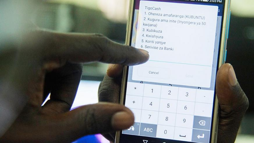 A customer uses TigoCash. The merger means that Airtel now has a combined customer base of 5.05 million users. (File)