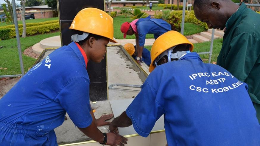 IPRC-East students lay tiles on Genocide memorial at their school. Hands-on skills are key to youth employment. (File)