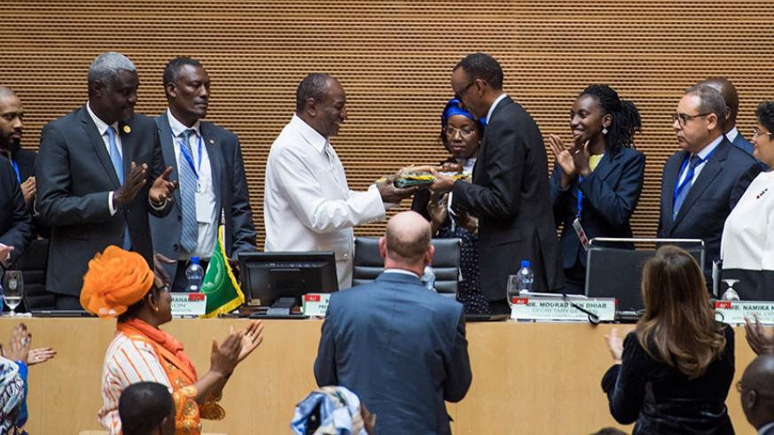 The outgoing Chairperson of the African Union, President Alpha Condé of Guinea (left), hands over to President Paul Kagame during the 30th AU Summit in Addis Ababa, Ethiopia yeste....