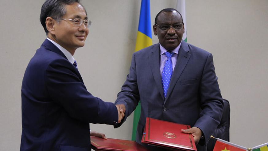 Chinese Ambassador to Rwanda Rao Hongwei and Finance and Economic Planning minister Claver Gatete exchange documents after signing a financing agreement in Kigali yesterday.  Sam N....
