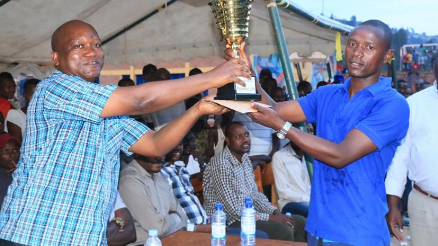 Police captain, Dismas Turatsinze hands over the trophy to the Deputy IGP in charge of Administration and Personnel, Juvenal Marizamunda