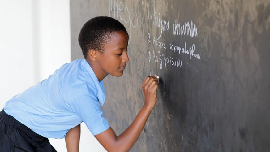 A pupil of Biryogo primary school writes on a blackboard during a lesson. Timothy Kisambira.