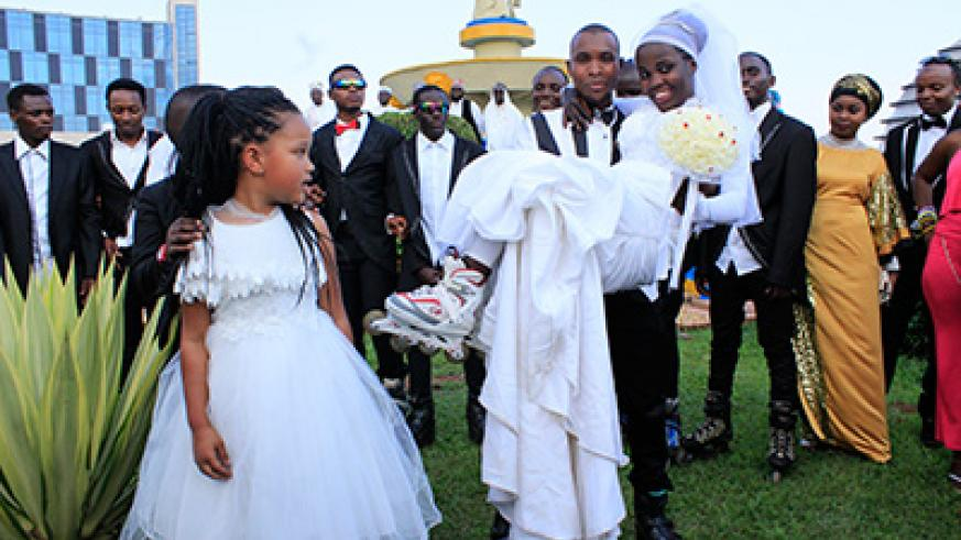 Habyarimana lifts his bride during a photo shoot on their wedding day. Courtesy