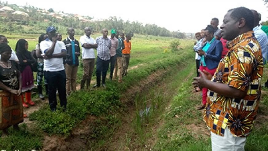 State minister for Agriculture, Fulgence Nsengiyumva (R) speaks to farmers and officials while assessing works at Rugende Marshaland last Friday. Emmanuel Ntirenganya.