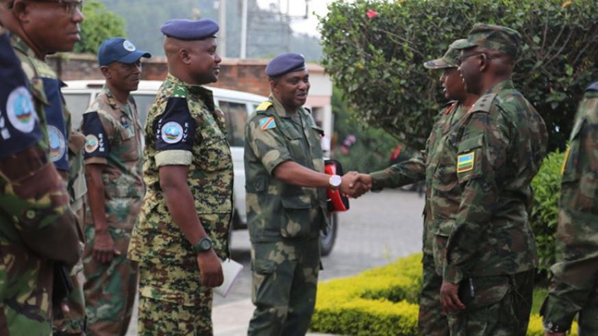 Brig Gen Eugene Nkubito (right) greets an officer from the EJVM at the RDF Second Division offices in Musanze on Thursday. Courtesy.