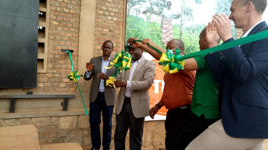 Nsengiyumva (in a black cap) cuts the ribbon to launch the fertiliser and seed wharehouse in Kayonza.  Emmanuel Ntirenganya.