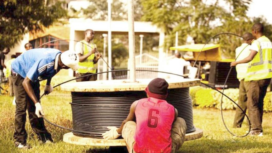Telecom workers install fibre optic cables in Kigali. File.