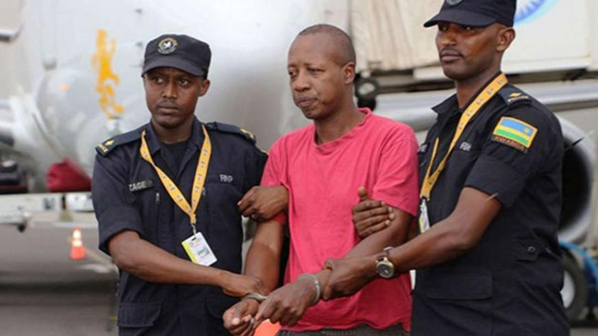Police officers arrest Genocide suspect Jean Twagiramungu at Kigali International Airport on his extradition from Germany in August last year. File.