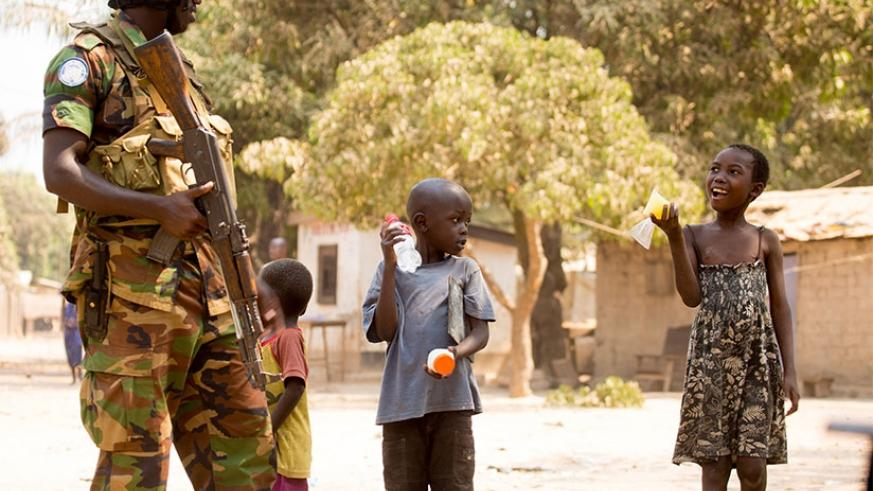 A Rwandan peacekeeper chats with children in Central Africa Republic. Timothy Kisambira.