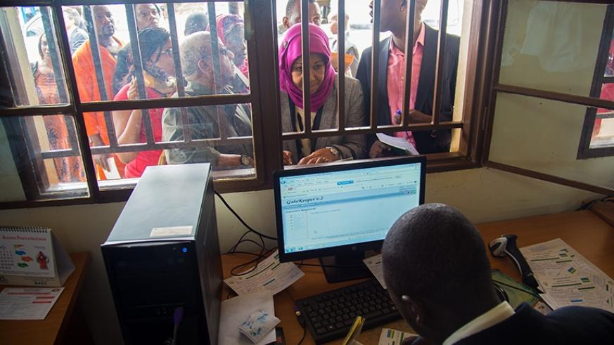 Travellers from Burundi to Rwanda present their documents to immigration officials at Nemba border post January 06 2015. File.