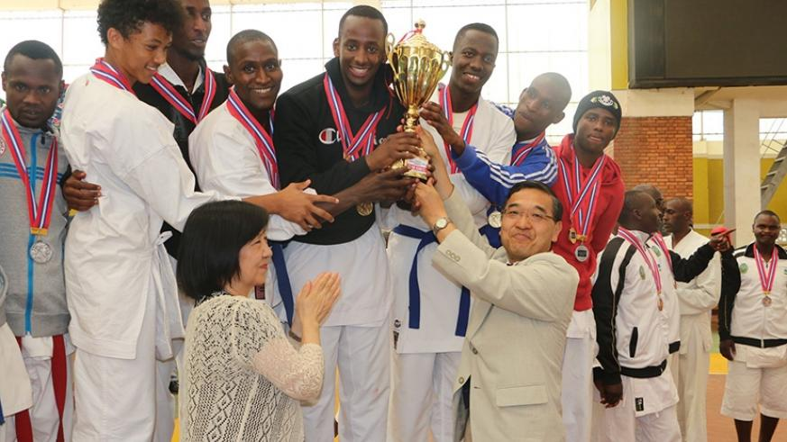 Vanily Ngarambe (in black sweater) seen here receiving the trophy from Japanese Ambassador at this year's Ambassador's Cup last month. Courtesy