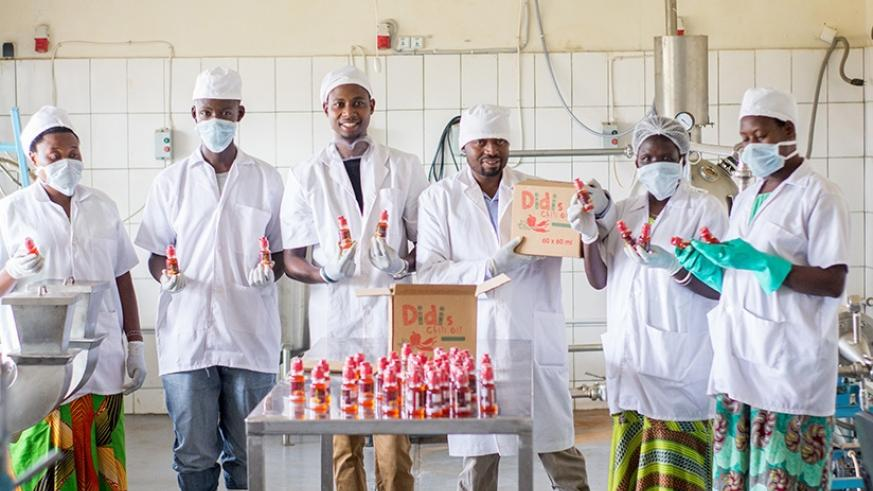 Twahirwa (2nd right) with his employees at the factory. (Courtesy)