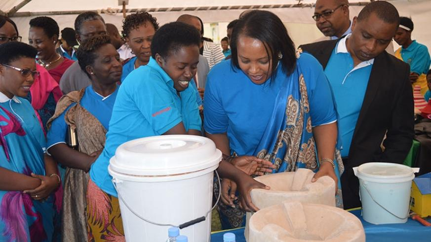 Minister Nyirasafari examines a water filter made from clay by a woman enterpreneur in Muhanga. Jean d'Amour Mbonyinshuti.