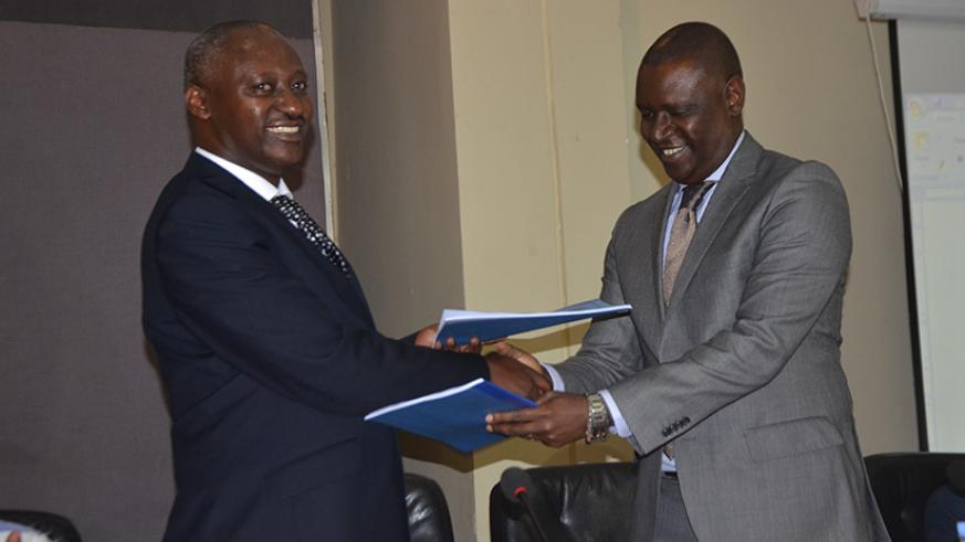 Robert Bafakulera the incoming PSF chairman exchanges documents with the outgoing chairman Benjamin Gasamagera. Courtesy