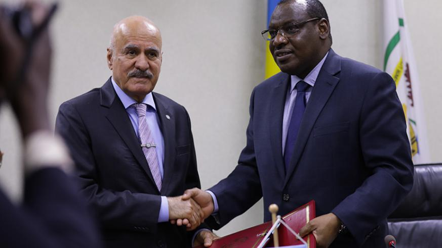 OFID Director-General Suleiman J Al- Herbish (L) exchanges documents with Claver Gatete, the Minister for Finance and Economic Planning, yesterday. Timothy Kisambira.