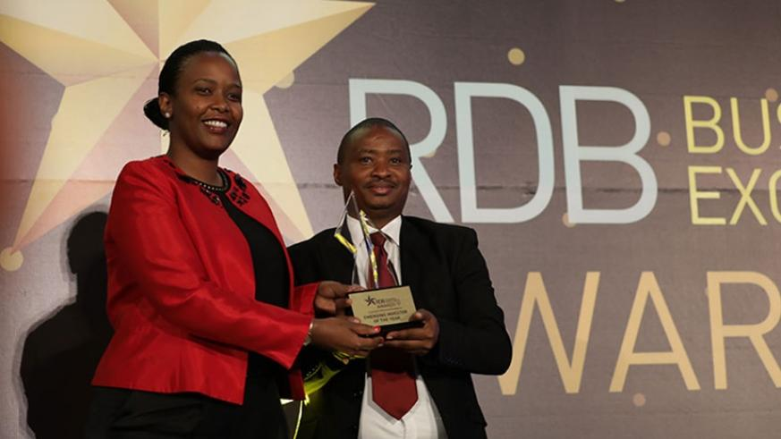 Chief Executive Officer of Rwanda Development Board gives an award of emerging investor of the year to Saudi Hitimana Human Resource manager of C&H.