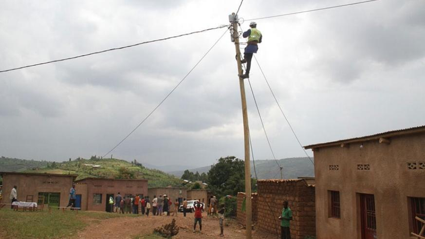 An EUCL worker connects residents onto the national grid in Nkuzuzu Cell, Bumbogo Sector in Gasabo District. (Photos by Timothy Kisambira)